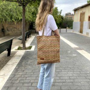 chica con el bolso de rafia colgado